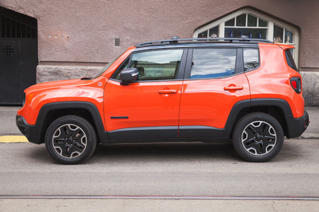 produced: Helsinki, Finland - May 21, 2016: New shining red Jeep Renegade, side view. It is a subcompact crossover SUV  or mini SUV in Europe, produced by Jeep