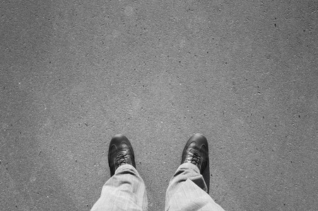 urbanite: Male feet in black new shining leather shoes standing on urban asphalt pavement