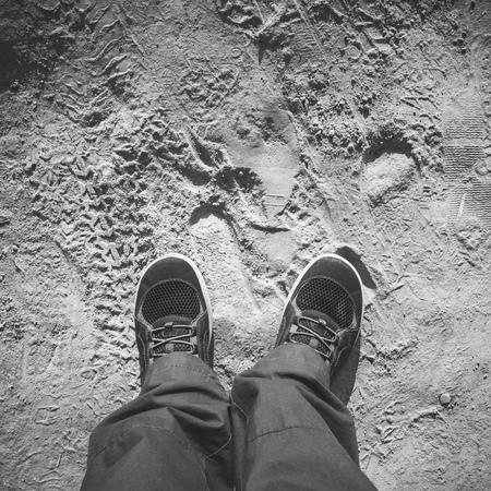 pies masculinos: Hombres pies en los zapatos deportivos se destacan en la carretera polvorienta sucia, vista en primera persona, cuadrado foto en blanco y negro