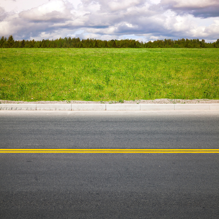 dividing lines: Empty highway roadside with yellow double dividing lines. Green summer grass and forest on a background