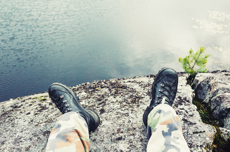 uniform green shoe: Male feet in camouflage pants and black rough shoes, travel lifestyle background. Cold tonal correction photo filter, old style effect