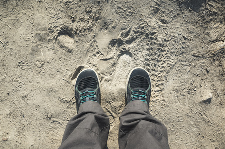 pieds sales: pieds m�les dans les chaussures sportives se tiennent sur la route sale poussi�reux, vue premi�re personne, filtre correction d'image tonale vintage, effet de style ancien Banque d'images