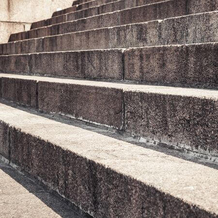 brown granite: Abstract architecture fragment. Old stairway made of brown granite stone blocks, closeup photo with selective focus Stock Photo