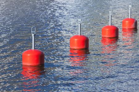 nautical equipment: Red mooring buoys in a row, European marina nautical equipment