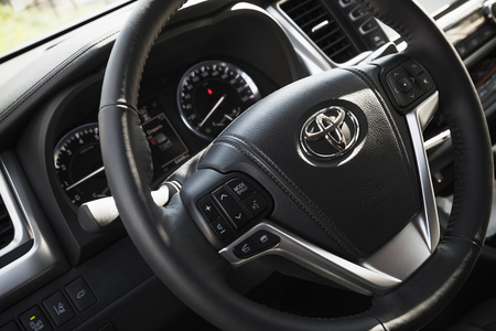 third wheel: St-Petersburg, Russia - May 12, 2016: Car wheel and dashboard, closeup photo with selective focus, Interior of luxury Japan crossover Toyota Highlander third generation, model of 2014 year Editorial