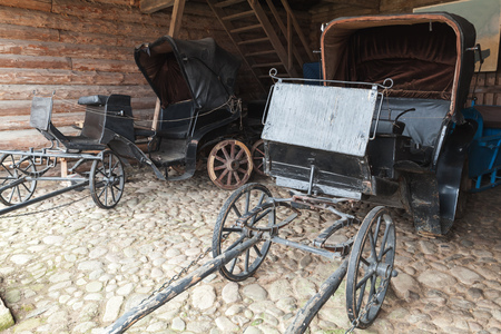 two car garage: Empty vintage black coaches stand in a rural garage