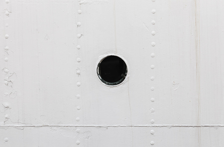 hull: Small round rusted porthole in old white ship hull