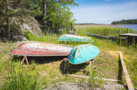 rowboats: Small rowboats lay upside down on the coast of still lake in reed Stock Photo