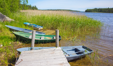 rowboats: Small rowboats lay on the coast of still lake near wooden pier