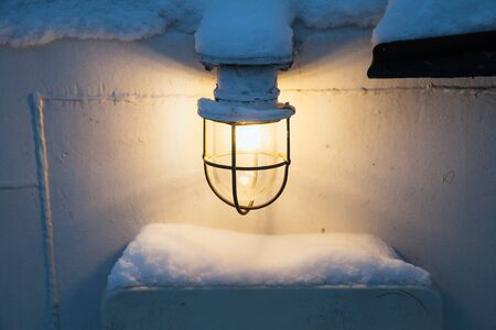 lampshade: Glowing lamp with warm light on white ship wall in winter Stock Photo