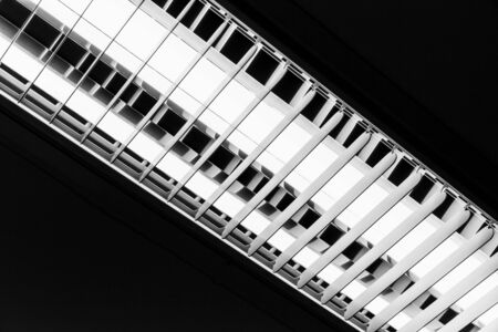 fluorescent tubes: White neon lamp glowing over black ceiling background
