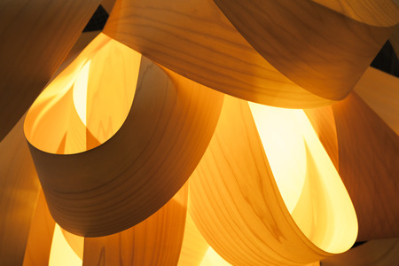 electric material: Abstract interior decoration background, lampshade made of wood veneer with bright glowing lamp inside, closeup photo with selective focus and shallow DOF Stock Photo