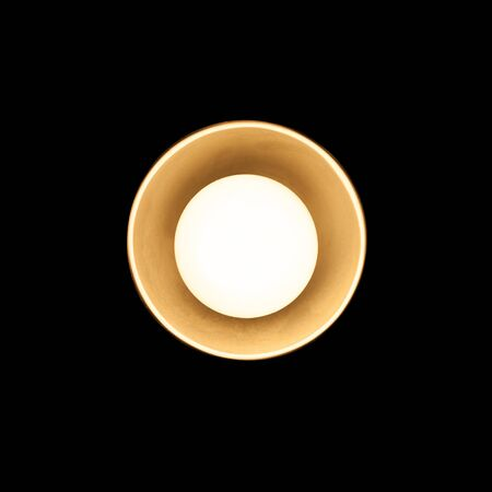 tungsten: Small tungsten lamp in metal lampshade glowing over black background, closeup photo Stock Photo
