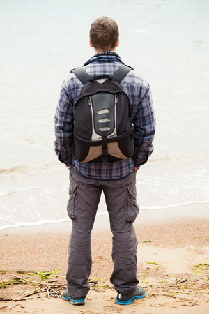 starring: Traveler on Baltic Sea coast. Young adult  Caucasian man in warm outdoor clothes with backpack starring at the sea, rear view Stock Photo