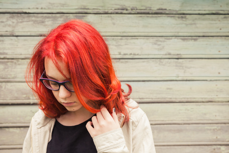calm woman: Caucasian teenager girl in glasses with bright red hair, closeup outdoor portrait over green grungy wooden wall Stock Photo