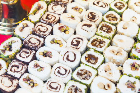 locum: Assortment of rolled Turkish delight. Traditional cuisines of the former Ottoman Empire, photo with selective focus Stock Photo