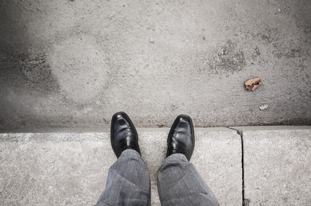curb: Feet of an urbanite man in black new shining shoes standing on gray curb