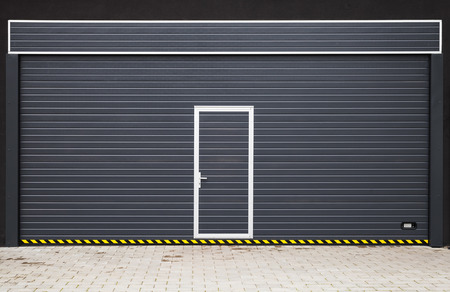 rolling garage door: Dark gray modern garage gate with small door in the middle, background photo texture Stock Photo