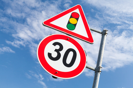 Traffic lights and speed limit 30 km per hour mounted on one metal post. Road signs over blue sky background