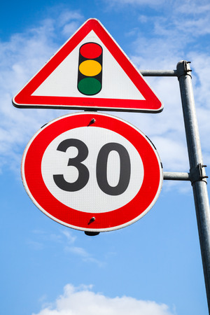 metal post: Traffic lights and speed limit 30 km per hour are on one metal post. Road signs over blue sky background