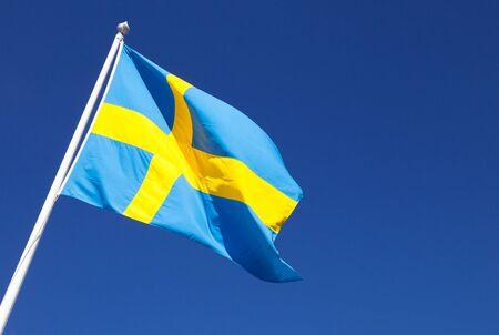 Waving on wind Swedish flag over deep blue sky background