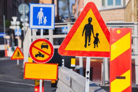 paso de peatones: Letreros de advertencia a lo largo de la carretera urbana europea en construcción Foto de archivo