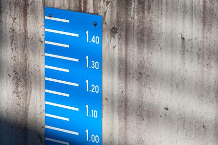 depth gauge: Blue tide level measurement scale on concrete mooring wall in port