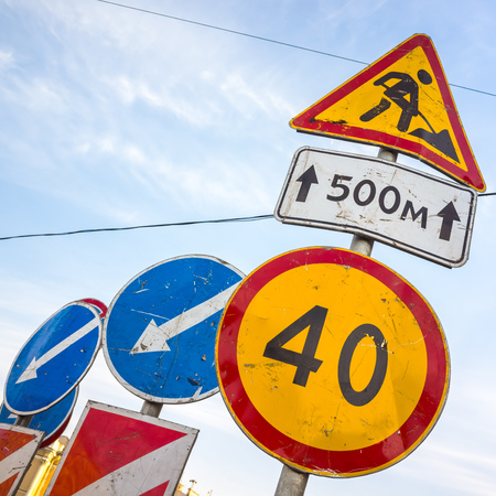 sky is the limit: Roadsigns over cloudy blue sky. Men at work, road under construction, speed limit 40 km per hour Stock Photo