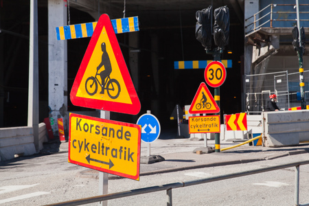 roadsigns: Warning roadsigns along urban road. Swedish text means intersecting bicycling