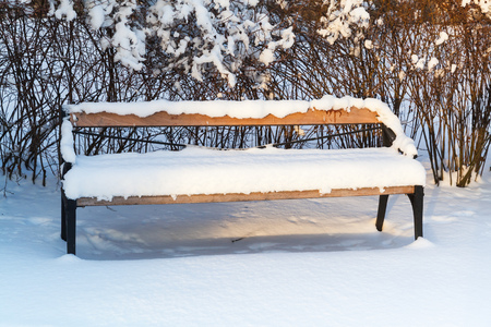 turku: Outdoor wooden bench covered with snow in winter park. Turku, Finland