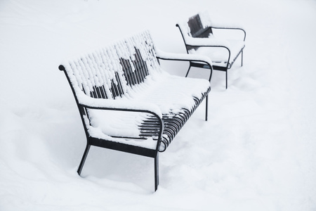 turku: Two outdoor metal benches covered with snow in winter park. Turku, Finland