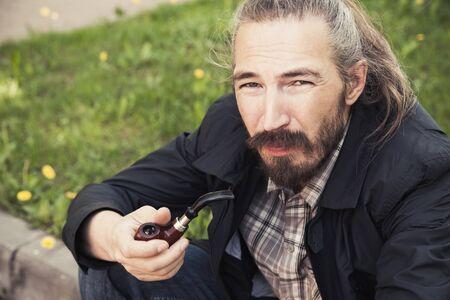 joven fumando: Asia hombre fumando una pipa en la hierba verde en el parque, foto de primer plano con un enfoque selectivo Foto de archivo