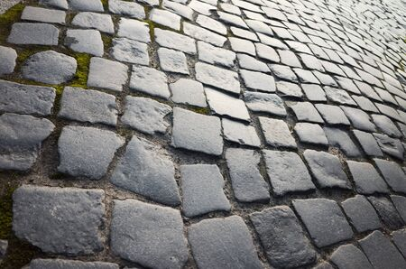 cobblestone road: Old dark gray shining cobblestone road background photo, vintage toned photo Stock Photo