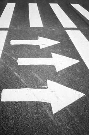 road marking: White arrows and stripes over black asphalt road, pedestrian crossing road marking zebra Stock Photo