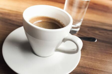 Cup of espresso coffee and small glass of fresh water stand on wooden table Stock Photo