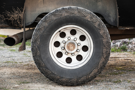 rusty car: SUV car wheel on dirty rural road, front view Stock Photo