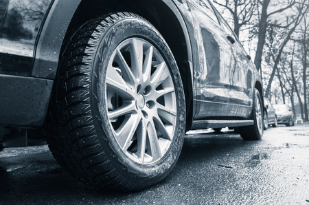alloy wheel: Fragment of black unidentifiable suv car, light alloy wheel with winter tires on dirty city road. Blue toned photo with selective focus Stock Photo