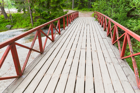 wooden railings: Wooden bridge with red railings over stream in summer park. Kotka, Finland