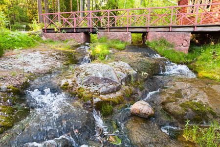Small wooden bridge with red railings over stream with waterfall in summer park. Kotka, Finland