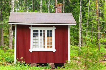 finland sauna: Small Scandinavian red wooden house over green forest background. Kotka, Finland Stock Photo
