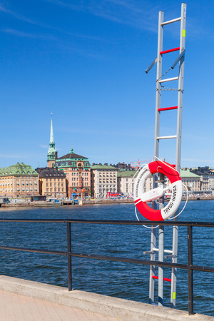 Stockholm, Sweden - May 5, 2016: Red and white ring buoy hanging on service metal ladder near embankment in central old part of Stockholm city