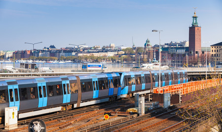 Stockholm, Sweden - May 4, 2016: Cityscape of Gamla Stan city district in central Stockholm with blue electric train going on bridge Editorial