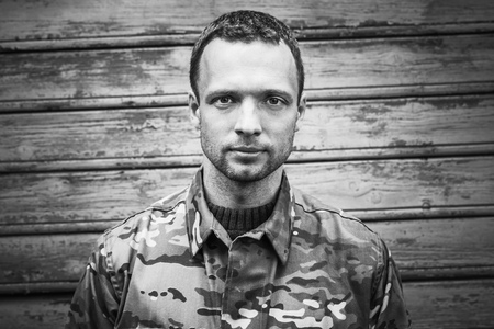 frontal portrait: Young Caucasian military man in camouflage uniform. Closeup black and white frontal portrait over wooden wall