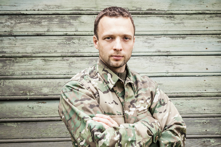 camoflauge: Young serious Caucasian military man in camouflage uniform with crossing hands. Closeup portrait over green wooden wall