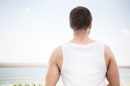starring: Young sporty Caucasian man in white shirt starring at the sea in summer day, rear view