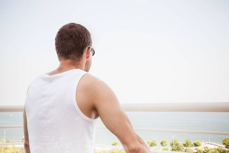 starring: Young sporty Caucasian man in white shirt and sunglasses starring at the sea in bright day, rear view Stock Photo