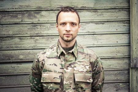 frontal portrait: Young serious Caucasian military man in camouflage uniform. Frontal portrait over green wooden wall Stock Photo