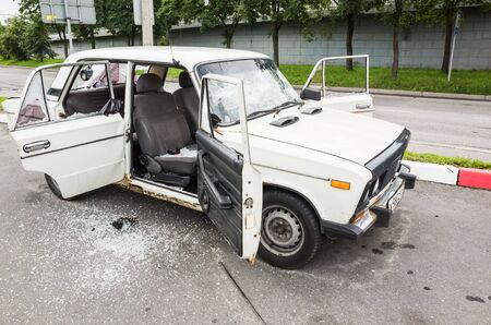 hijacked: Saint-Petersburg, Russia - August 6, 2016: Crushed white VAZ-2106 car with broken windows and smashed doors Editorial