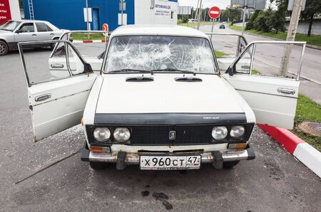 hijacked: Saint-Petersburg, Russia - August 6, 2016: Crushed white VAZ-2106 car with broken windows and smashed doors, front view