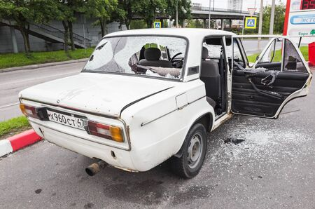 hijacked: Saint-Petersburg, Russia - August 6, 2016: Crushed white VAZ-2106 car with broken windows and smashed doors, rear view